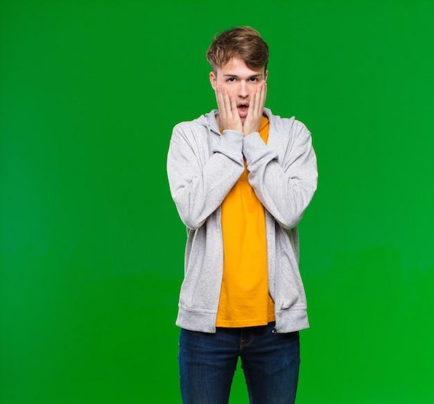 若いブロンドの男性がショックを受けて怖がって感じ、口を開けて、クロマキーの壁に頬に手を当てて怖がって