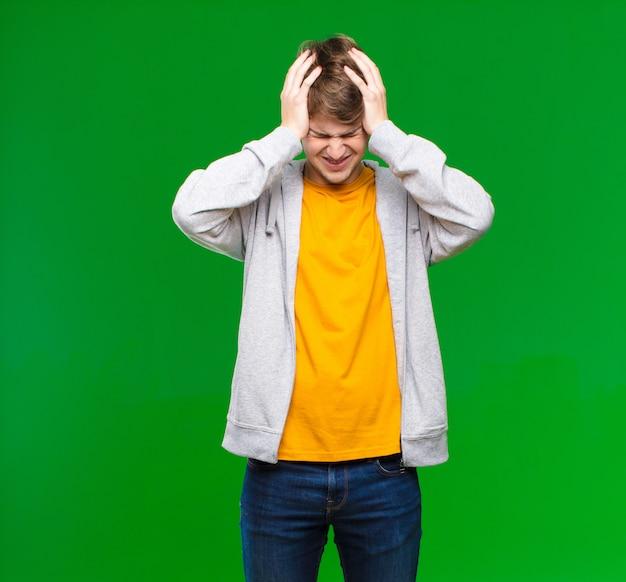 Молодой блондин чувствует стресс и разочарование, поднимает руки к голове, чувствует себя усталым, несчастным и страдает мигренью у стены с хромакей