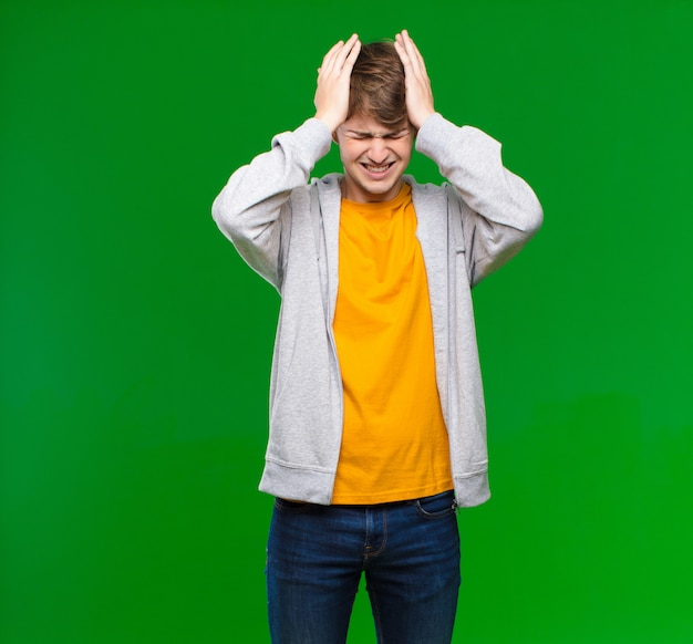 Young blonde man feeling stressed and anxious, depressed and frustrated with a headache, raising both hands to head on chroma key wall