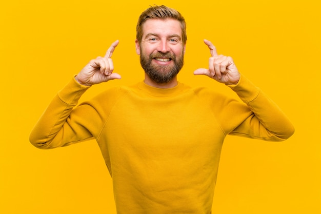 Young blonde man framing or outlining own smile with both hands, looking positive and happy, wellness   orange wall