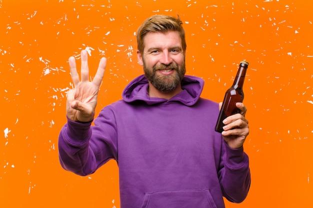 Young blonde man having a beer wearing a purple hoodie against damaged orange wall