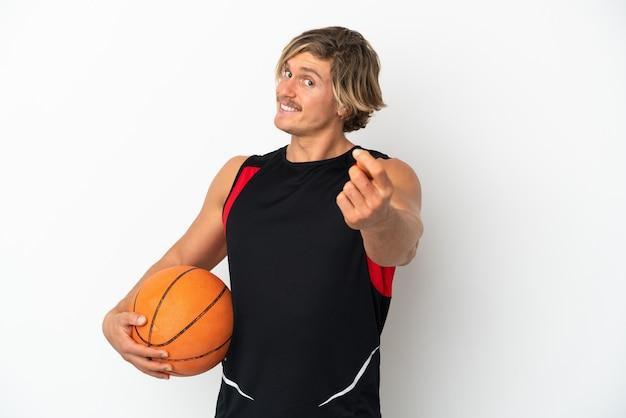 Молодой блондин, держащий баскетбольный мяч, изолированный на белой стене, делая денежный жест