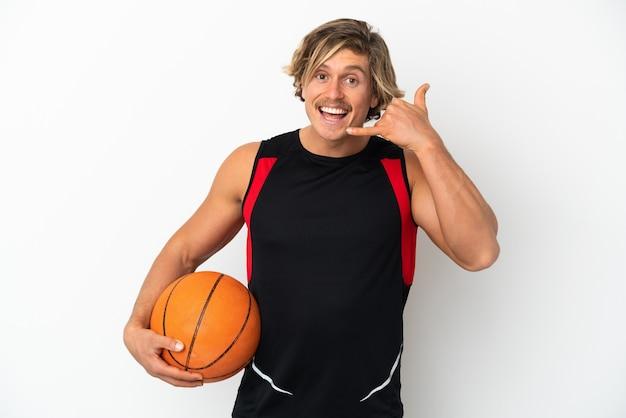 電話のジェスチャーを作る白い壁に分離されたバスケットボールのボールを保持している若いブロンドの男。コールバックサイン