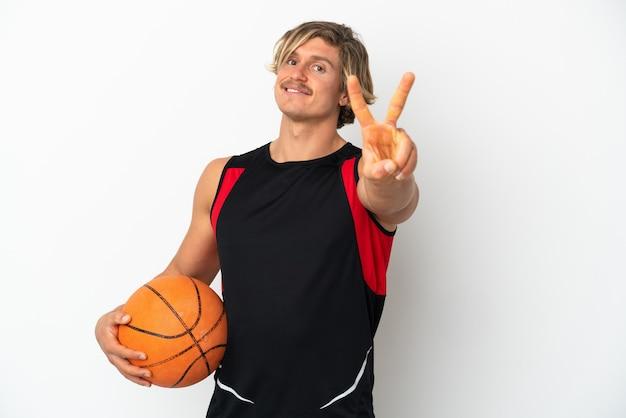 웃 고 승리 기호를 보여주는 흰 벽에 고립 된 농구의 공을 들고 젊은 금발의 남자