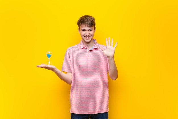 Young blonde man holding a sandclock timer
