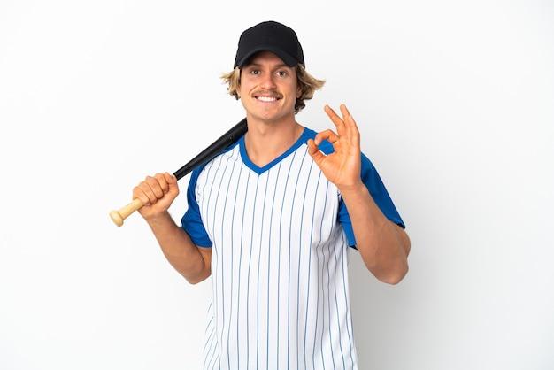 야구를 하 고 손가락으로 확인 표시를 보여주는 흰색 배경에 고립 된 젊은 금발의 남자
