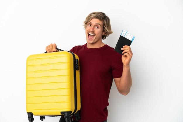 가방 및 여권 휴가에 흰 벽에 고립 된 젊은 금발의 남자