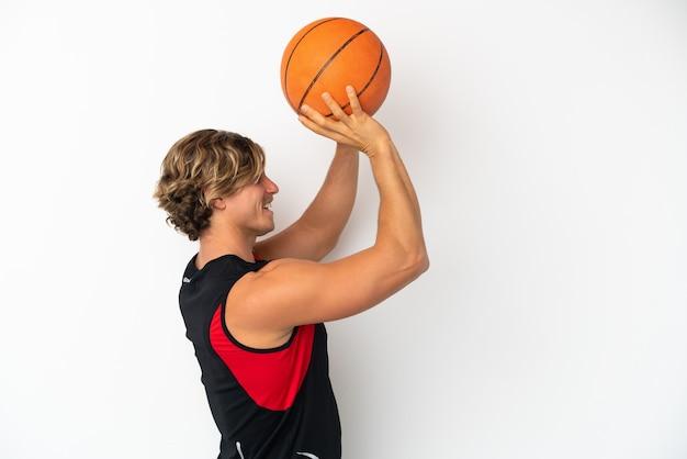 Молодой блондин, изолированный на белой стене, играет в баскетбол