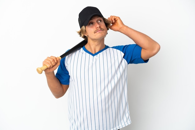 Young blonde man isolated on white wall playing baseball and having doubts with confuse face expression
