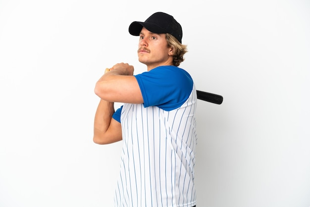 Young blonde man isolated on white wall playing baseball