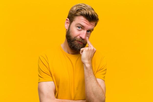 Молодой белокурый мужчина следит за тобой, не доверяя, наблюдая и оставаясь настороже и бдительно оранжевая стена