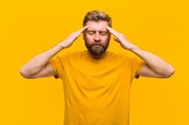 Young blonde man looking concentrated, thoughtful and inspired, brainstorming and imagining with hands on forehead on orange wall
