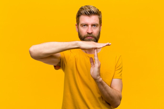 Young blonde man looking serious, stern, angry and displeased, making time out sign  orange wall
