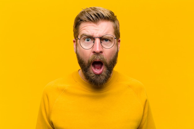 Young blonde man looking shocked, angry, annoyed or disappointed, open mouthed and furious against orange wall