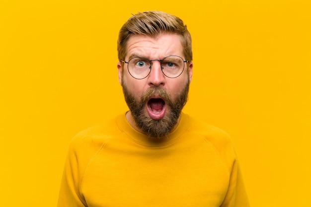 충격, 화가, 짜증 또는 실망을 찾고 젊은 금발의 남자는 오렌지 벽에 입을 열고 분노