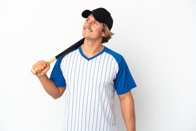 Молодой блондин, играя в бейсбол, изолированные на белом фоне, думая об идее, глядя вверх