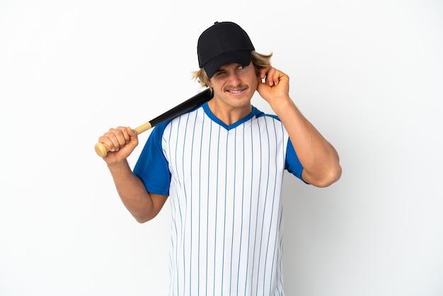 欲求不満と耳を覆っている白い壁に孤立した野球をしている若いブロンドの男