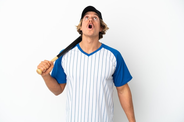 Young blonde man playing baseball isolated on white background looking up and with surprised expression