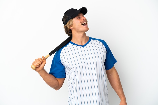 Young blonde man playing baseball isolated on white laughing