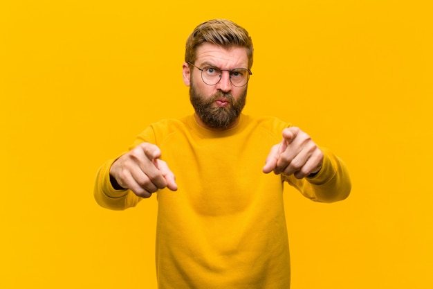 Young blonde man pointing forward at camera with both fingers and angry expression