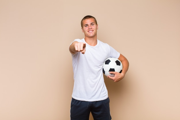 Young blonde man pointing at front with a satisfied, confident, friendly smile, choosing you