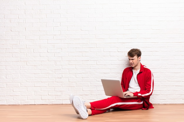 Young blonde man sitting on the floor with a laptop