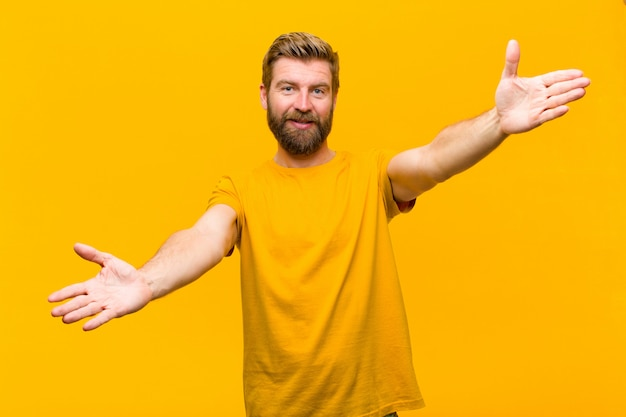 オレンジ色の壁に対して幸せと愛らしい感じ、暖かく、友好的、愛情のある歓迎抱擁を与えて元気に笑顔若い金髪男