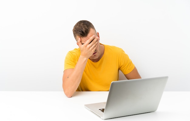 Young blonde man in a table with a laptop covering eyes by hands