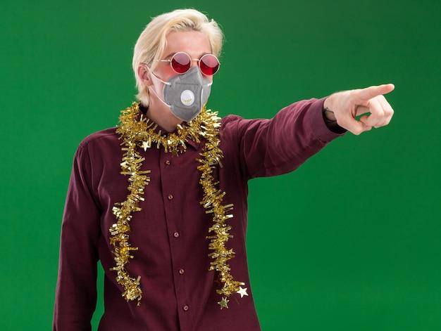 Giovane uomo biondo con gli occhiali e maschera protettiva con la ghirlanda di orpelli intorno al collo guardando e indicando il lato isolato sulla parete verde
