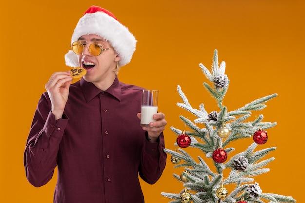 Giovane uomo biondo che porta il cappello e gli occhiali della santa che stanno vicino all'albero di natale decorato che tiene il bicchiere di latte e biscotto vicino alla bocca con gli occhi chiusi isolati sulla parete arancione