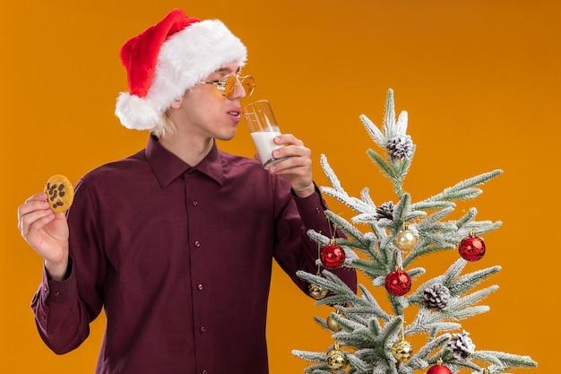 Giovane uomo biondo che indossa cappello santa e occhiali in piedi vicino all'albero di natale decorato che tiene il bicchiere di latte vicino alla bocca e biscotto con gli occhi chiusi