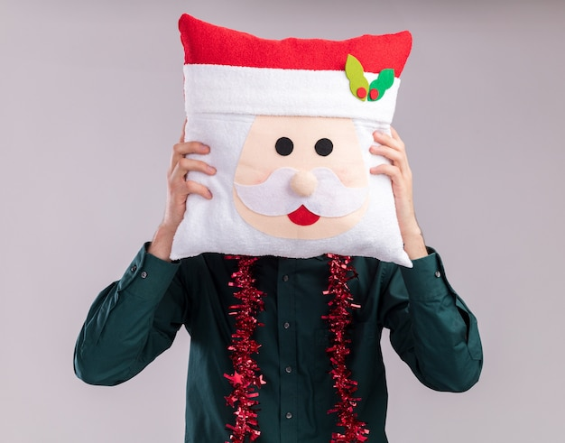Young blonde man wearing santa hat and glasses with tinsel garland around neck holding santa claus pillow covering face with it isolated on white background