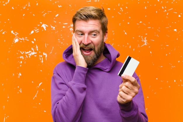 Young blonde man with a credit card  wearing a purple hoodie against damaged orange wall