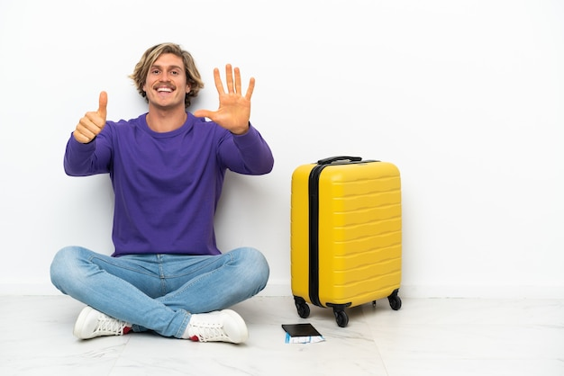 Young blonde man with suitcase sitting on the floor counting six with fingers