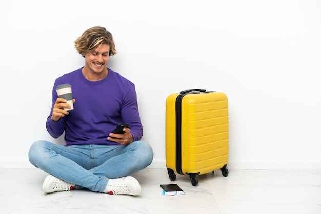 Young blonde man with suitcase sitting on the floor holding coffee to take away and a mobile