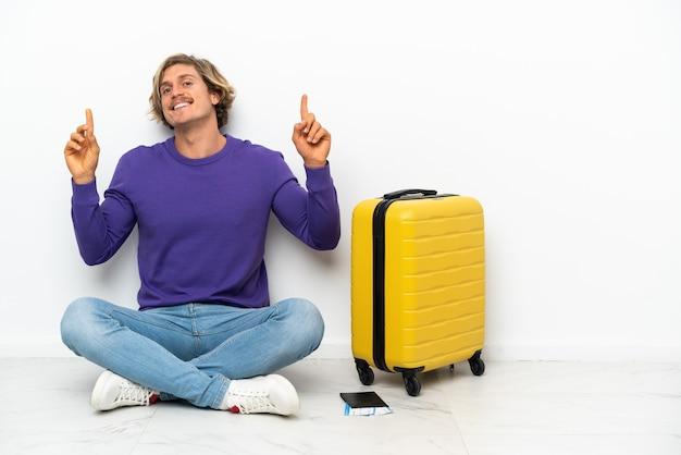 Young blonde man with suitcase sitting on the floor pointing up a great idea
