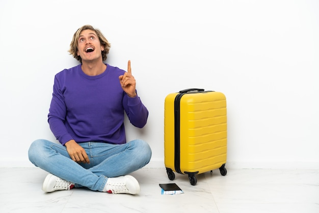 Young blonde man with suitcase sitting on the floor pointing up and surprised