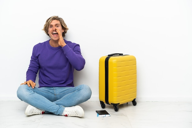 Young blonde man with suitcase sitting on the floor shouting with mouth wide open