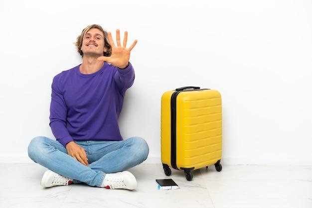 가방 손가락으로 5 세 바닥에 앉아 젊은 금발의 남자