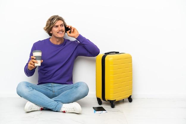 持ち帰り用のコーヒーと携帯電話を持って床に座っているスーツケースを持つ若いブロンドの男
