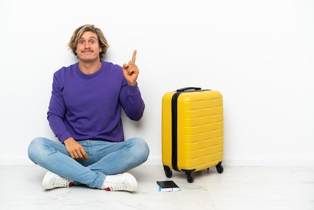 人差し指で指している床に座っているスーツケースを持つ若いブロンドの男素晴らしいアイデア