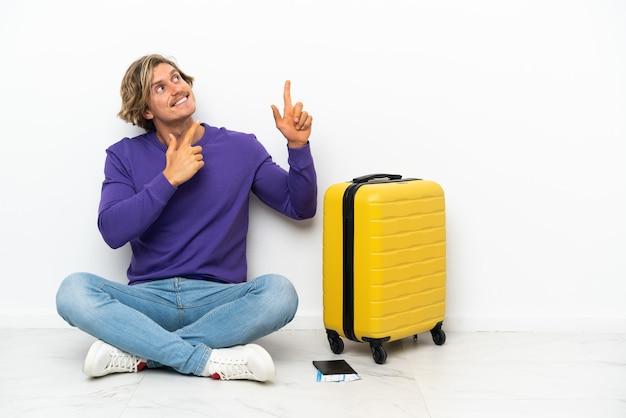 ポインティング床に座っているスーツケースを持つ若いブロンドの男