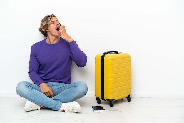 あくびをし、手で大きく開いた口を覆って床に座っているスーツケースを持つ若いブロンドの男