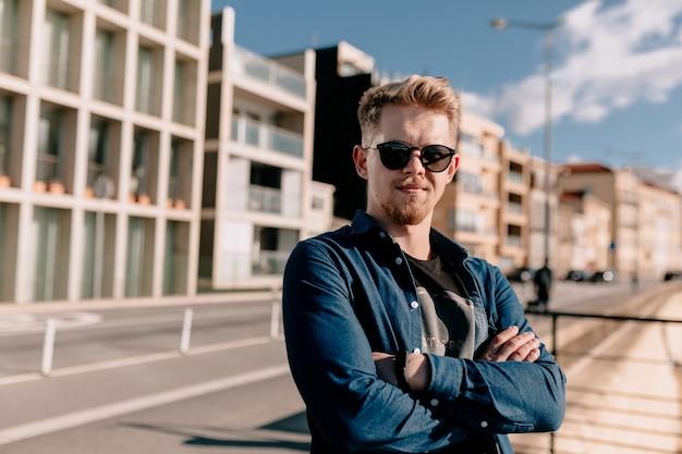 Giovane uomo biondo con occhiali da sole in posa sulla strada