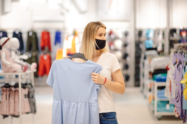Young blonde in mask in shopping center chose beautiful  blue dress made of natural materials