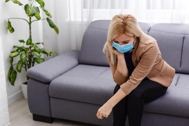 Молодая блондинка в маске беспокоится о карантине. коронавирус, болезнь, инфекция, карантин, хирургическая повязка.