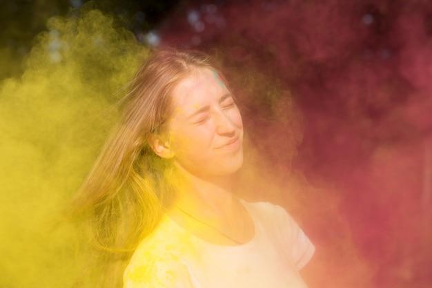 色のホーリー祭でカラフルなペイントを楽しんでいる若い金髪モデル