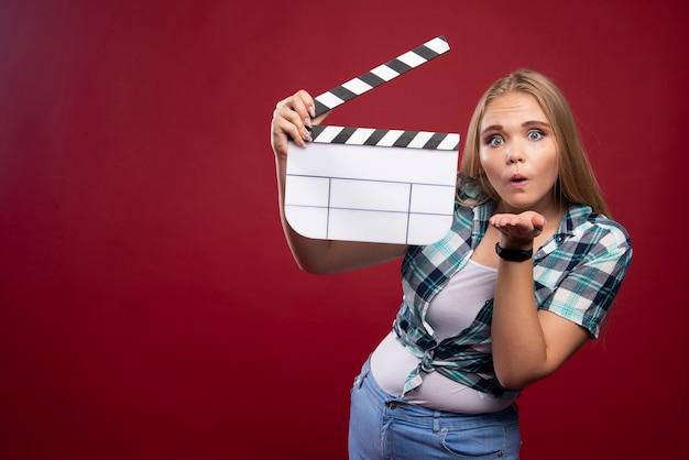 Молодая блондинка модель держит пустую доску с хлопушкой для съемок фильма и развлекается.