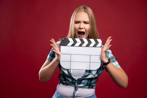 Молодая блондинка модель держит пустую доску с хлопушкой для съемок фильма и выглядит недовольной.