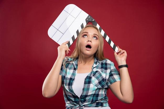 Молодая белокурая модель держит пустую доску с хлопушкой для съемок фильма и выглядит напряженной и неопытной.